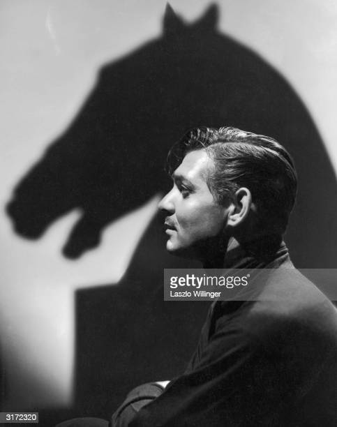 American leading man Clark Gable in profile with a shadow of a horse's head on the wall behind him