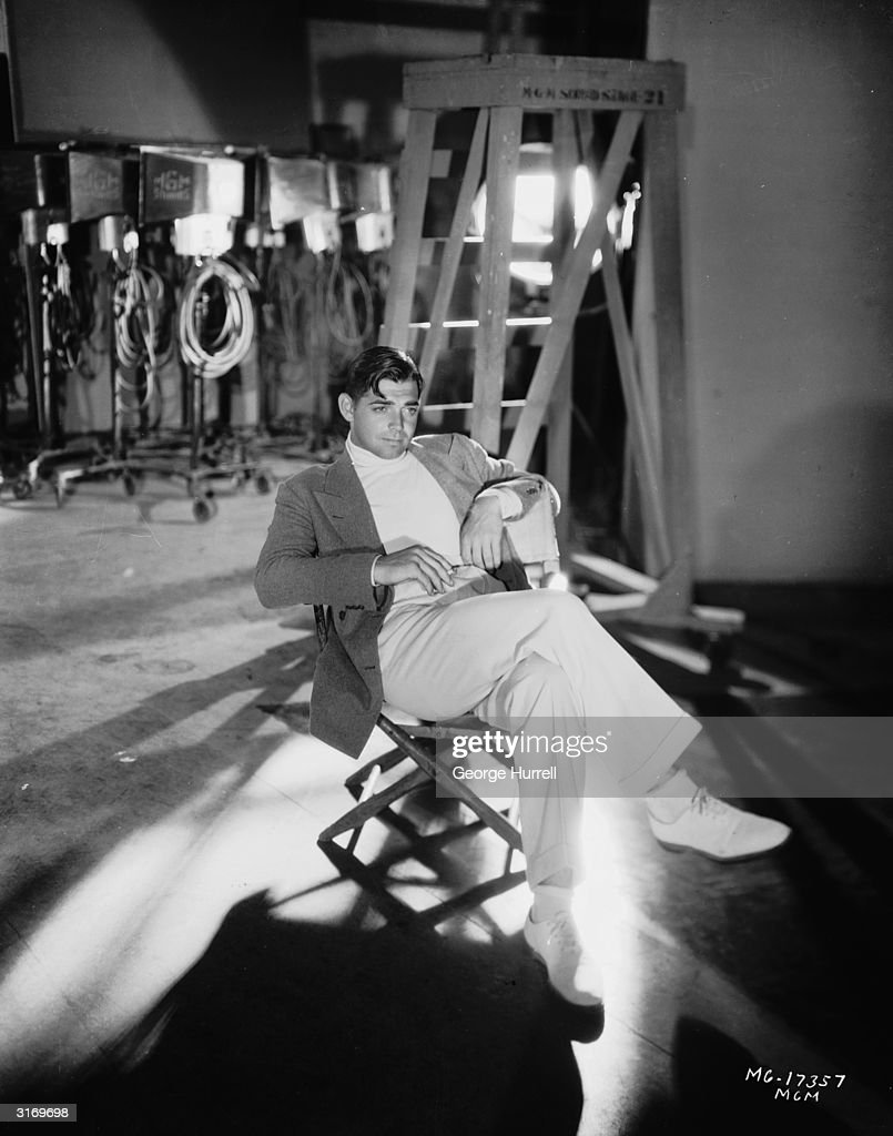American leading man Clark Gable (1901 - 1960) slouches in a studio chair.