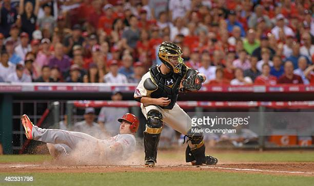 American League AllStar Mike Trout of the Los Angeles Angels of Anaheim slides safely into home while National League AllStar Buster Posey of the San...