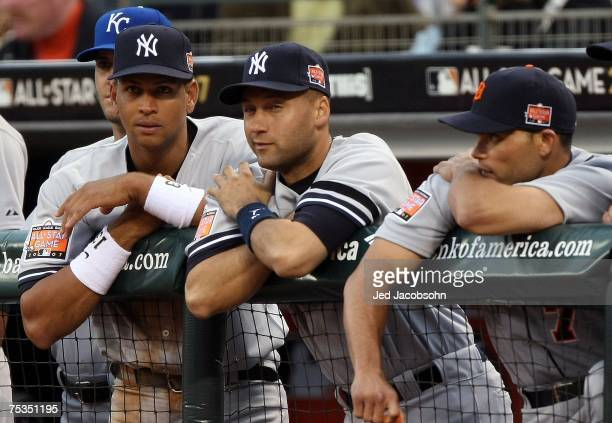 American League AllStars Alex Rodriguez Derek Jeter of the New York Yankees and Ivan Rodriguez of the Detroit Tigers talk in the dugout during the...