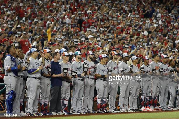 American League AllStars and fans hold up Stand Up 2 Cancer signs during the 89th MLB AllStar Game presented by Mastercard at Nationals Park on July...