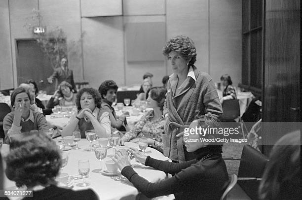 American literary agent and publisher Joni Evans, hands in her pockets, stands at a table during a women's lunch, New York, New York, 1977.