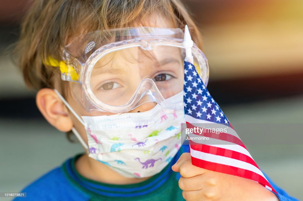 American little caucasian boy posing with a protective mask, protective glasses holding a US flag : Stock Photo