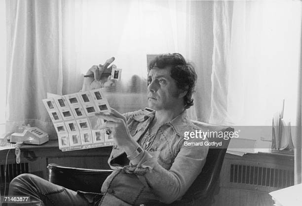 American magazine publisher Bob Guccione wears a leather shirt and a lot of chains around his neck as he reviews transparencies for 'Penthouse...