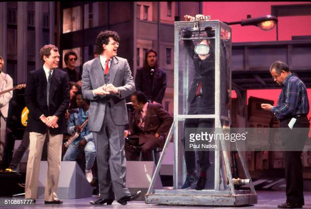American magicians Penn and Teller perform a card trick with a water tank on and episode of the Late Night with David Letterman television show...