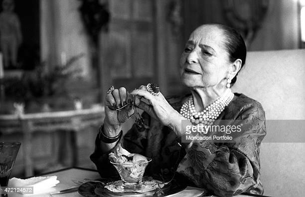 'American magnate Helena Rubinstein sitting at a laid table has just finished a frugal meal in the luxurious dining room of her house on the Fifth...