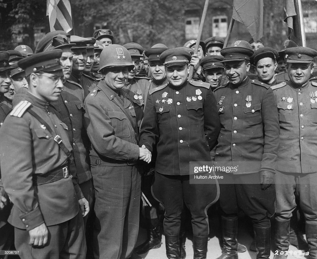 American Major-General Emil F. Reinhardt (1888 - 1969) (second left), Commanding General of the 69th Division, shakes hands with his Russian counterpart, Major-General Vladimir V. Rusakov, Commanding Officer of the 58th Guards Division, at a meeting of American and Russian troops near the Elbe River and the town of Torgau, Germany, late April, 1945. The two armies had met up on the 25th pf April, effectivrly splitting the opposing German army.