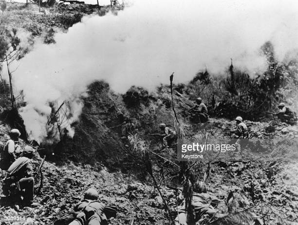 American Marines advance on trapped Japanese soldiers bombed during the Battle for Okinawa.
