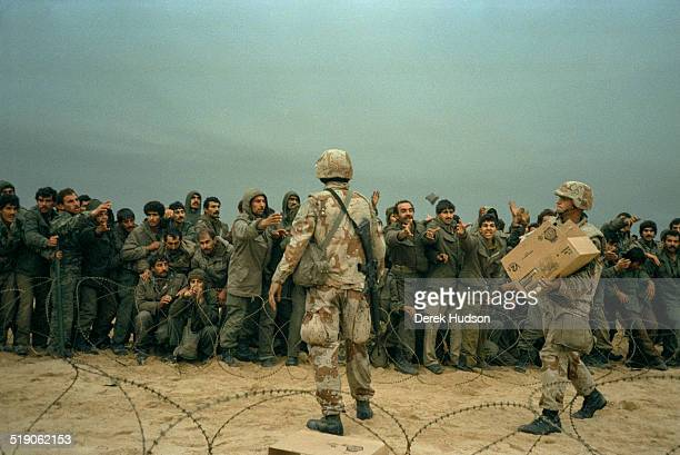 American Marines distribute MRE rations to several hundred captured Iraqi soldiers, throwing the packs in the air to be fought over by the prisoners,...