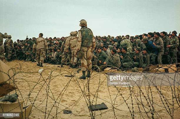 American Marines distribute MRE rations to several hundred captured Iraqi soldiers throwing the packs in the air to be fought over by the prisoners...