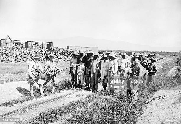 American Marines guard Haitian outlaws they captured outside PortauPrince The United States had invaded Haiti in 1915 to restore order and to protect...