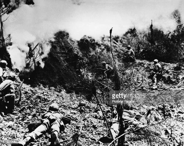 American marines keep their weapons trained on the entrance to a cave into which they have thrown an explosive device to flush out Japanese defenders...