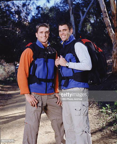 American married game show contestants Chip Arndt & Reichen Lehmkuhl, both dressed in cargo pants and fleece vests & carrying backpacks, smile as...