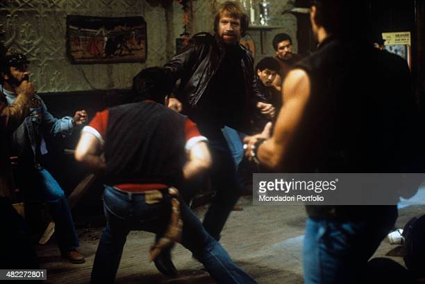 American martial artist and actor Chuck Norris fighting against a group of men in the film Code of Silence 1985