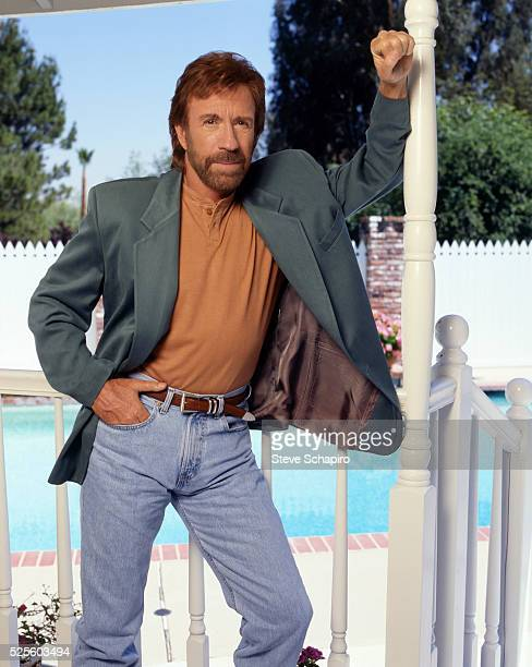 American martial artist and actor Chuck Norris poses with one hand in his pocket, the other leaning against an upright, circa 1980.