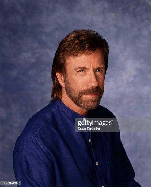 American martial artist and actor Chuck Norris wearing a blue collarless shirt in a studio portrait circa 1980