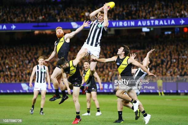American Mason Cox of the Magpies marks the ball against Nick Vlastuin Trent Cotchin and Alex Rance of the Tigers during the AFL Preliminary Final...