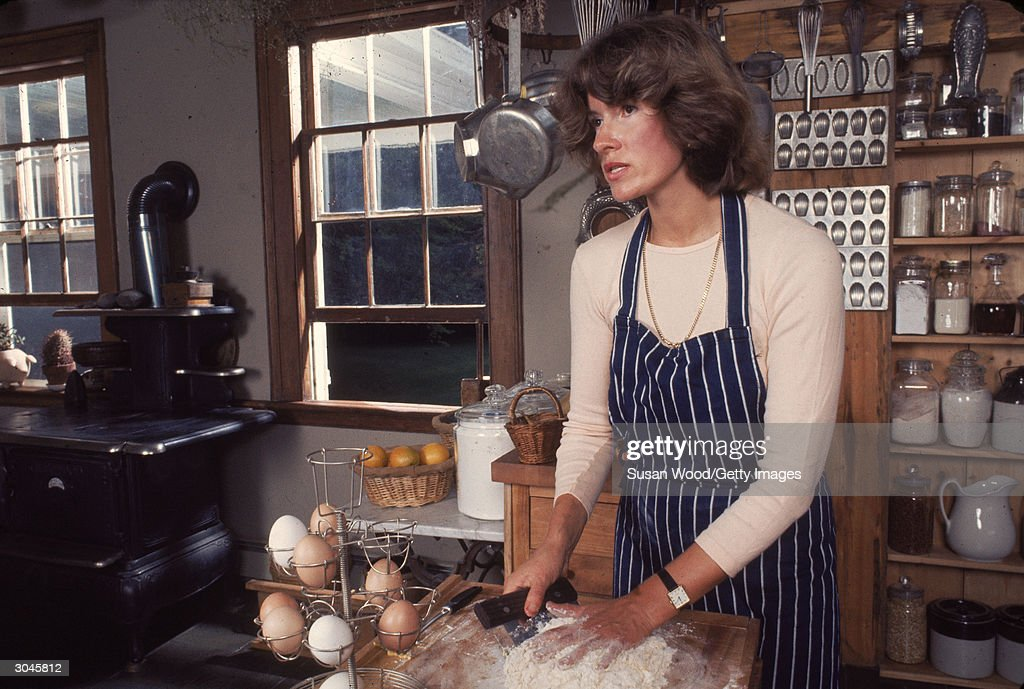 American media mogul and businesswoman Martha Stewart kneads flour in a fully-stocked kitchen, August 1976.