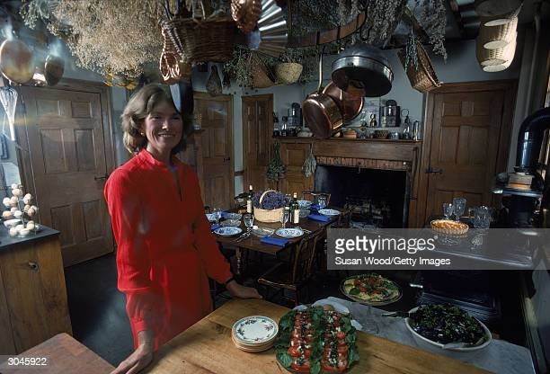 American media mogul and businesswoman Martha Stewart stands in a kitchen in a red dress August 1976 Behind her is a table set with plates wine...
