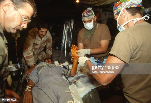 American medics attend to an injured man inside a medical tent during the Gulf War Iraq 1991