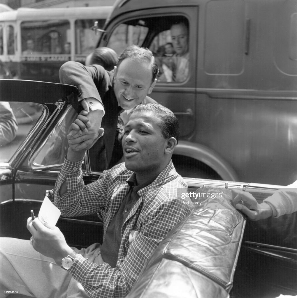 American middleweight boxer Sugar Ray Robinson (1921-1989), who became the welterweight and middleweight boxing champion of the world, on his way to England to fight Randolph Turpin, sitting in his car in Paris and shaking hands with an autograph-hunter. Original Publication: Picture Post - 5350 - Sugar Ray - pub. 1951