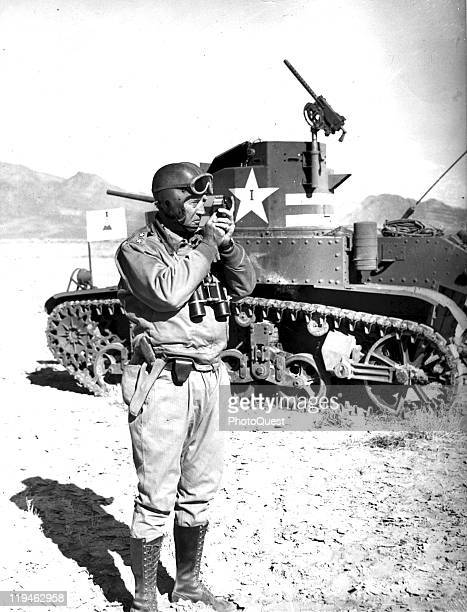 American military commander General George S. Patton checks range as he stands next to a tank during training maneuvers, 1942.