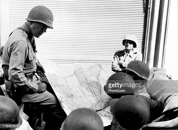 American military commander Lieutenant General George S. Patton , Commander of the US 7th Army, confers with unidentified officers during the...