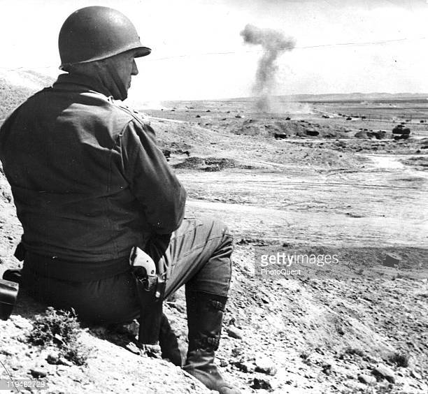 American military commander Lieutenant General George S Patton sits on the sand and watches a tank battle in Tunisia 1943