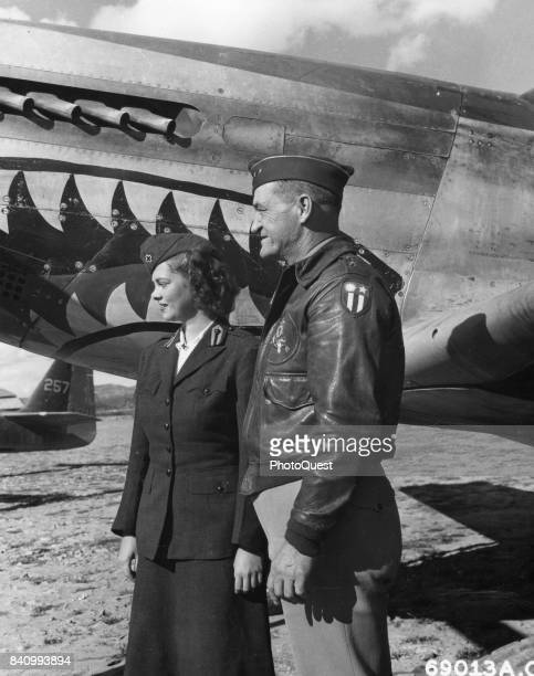 American military commander Maj Gen Claire L Chennault stands with an unidentified American Red Cross volunteer in front of a North American P51...