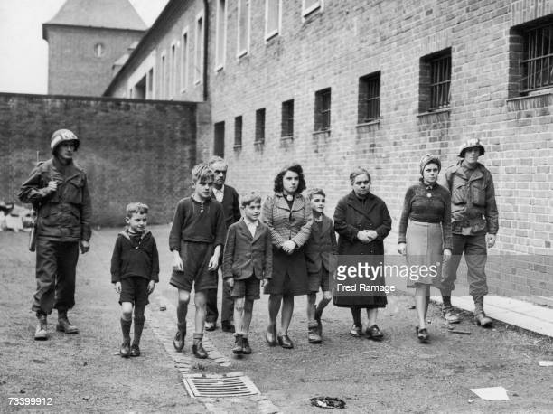 American military police officers with 14 yearold Willy Etschenberg and members of his family in a prison courtyard in Aachen October 1944...