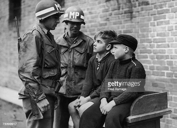 American military police officers with 14 yearold Willy Etschenberg and 10 yearold Hubert Heinrichs who are being held after sniping at US troops in...