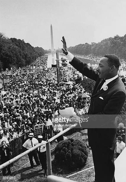 American minister and civil rights leader Dr Martin Luther King Jr waves to the crowd of more than 200000 people gathered on the Mall after...