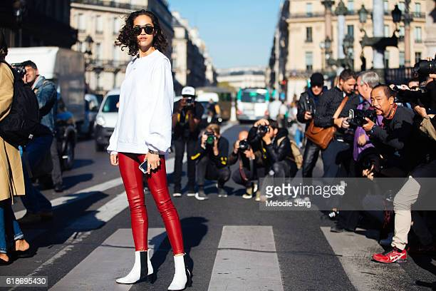 American model Alanna Arrington poses for photographers and wears a white OffWhite sweatshirt red leather leggings and white booties after the Stella...