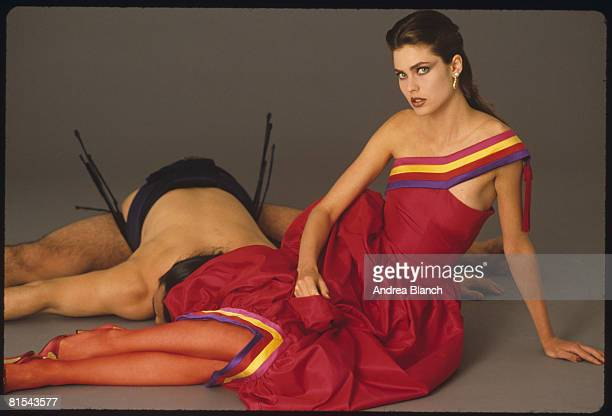 American model and actress Carol Alt sits next to a defeated sumo wrestler for a magazine photoshoot 1980