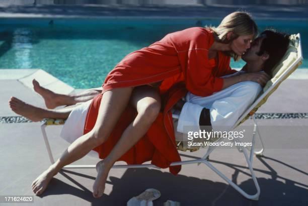American model and actress Cheryl Tiegs kisses her husband film director Stan Dragoti beside a pool at La Costa Resort Spa Carlsbad California...
