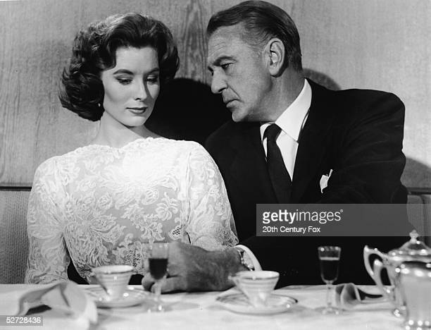 American model and actress Suzy Parker and actor Gary Cooper share an intimate momement over a drink in a scene from Philip Dunne's film 'Ten North...