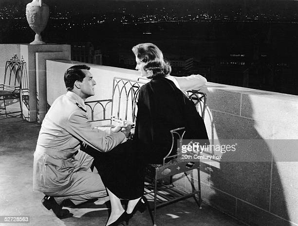 American model and actress Suzy Parker and Britishborn actor Cary Grant share an intimate moment in a scene from Stanley Donen's 'Kiss Them for Me'...
