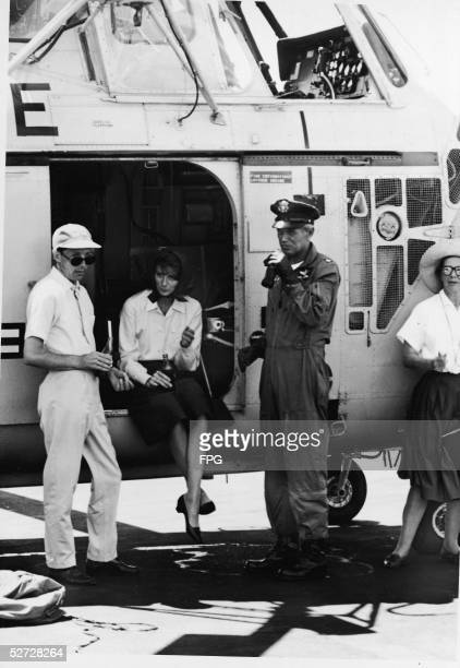 American model and actress Suzy Parker sits in the door of a Sikorsky S58T helicopter and drinks a coke alongside costar Richard Widmark and two crew...