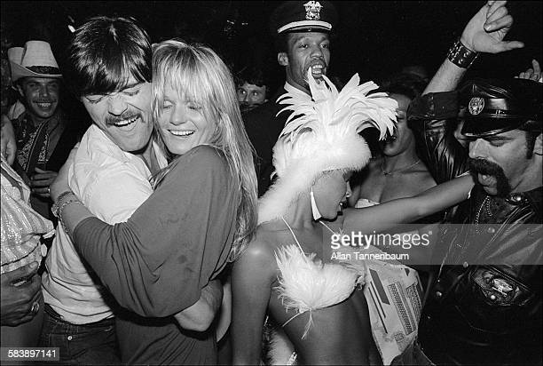 American model and actress Valerie Perrine dances with musicians David Hodo Alex Briley and Glenn Hughes all of the group the Village People during...