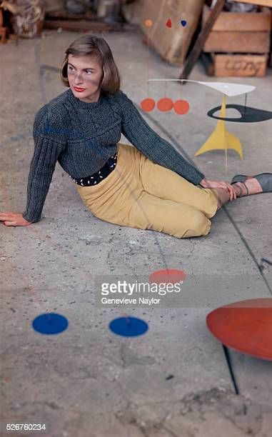 American model and fashion editor Jessica Patton Barkentin in suede pedal pushers and a sweater behind one of Alexander Calder's mobiles at the...