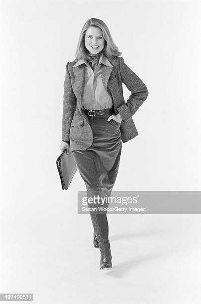 American model Christie Brinkley poses, dressed in business attire, against a white background, 1976. She wears a neckerchief, a tweed jacket over a...