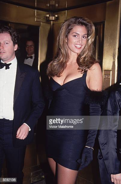 American model Cindy Crawford smiles while at the 'Vogue' magazine 100th anniversary party New York City She wears a black mini Herve Leger 'bandage'...