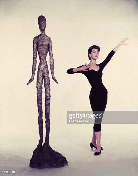 American model Dovima poses next to a sculpture of a woman in a still from director Stanley Donen's film 'Funny Face'