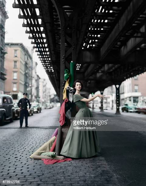 American model Dovima posing in a Christian Dior dress with rolls of fabric under the Elevated railway 3rd Avenue New York 1956 For 'Dior Creates...