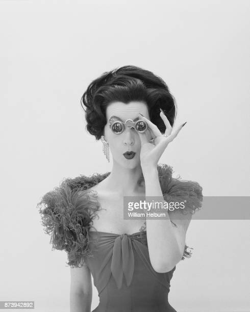 American model Dovima posing with opera glasses and an ostrich feather boa circa 1961