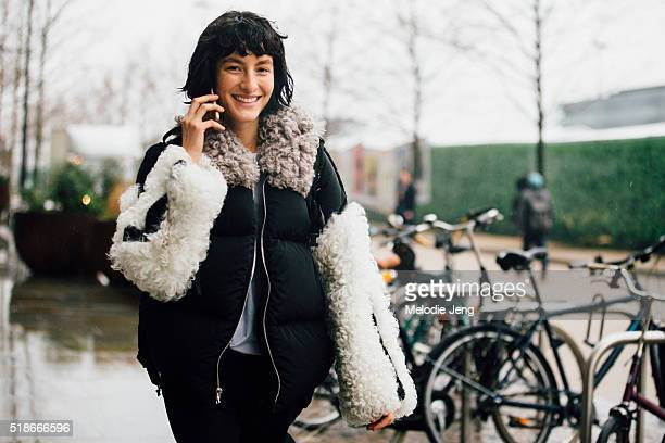 American model Heather Kemesky makes a phone call and wears a Sandy Liang Allen puffer jacket with a shearling sleeve and collar after the Anya...