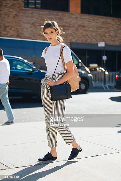 American model Zuzu Tadeushuk wears a white shirt tan backpack black and white striped ankle trousers a Phillip Lim bag and Phillip Lim flat mule...