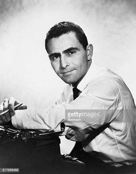 American motion picture producer and screenwriter Rod Serling leans on a typewriter.
