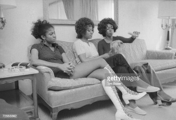 American Motown singing group The Supremes Jean Terrell Cindy Birdsong and Mary Wilson hold and taunt with food a small dog as they sit on a couch...