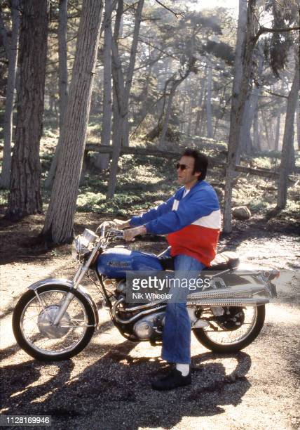American movie actor and director Clint Eastwood poses for a portrait on his Norton Motorbike at home in Pebble Beach Carmel California